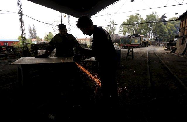 "Mechanics work in the ""La Sabana"" tourist train workshop in Bogota, March 2, 2015. (Photo by Jose Miguel Gomez/Reuters)"