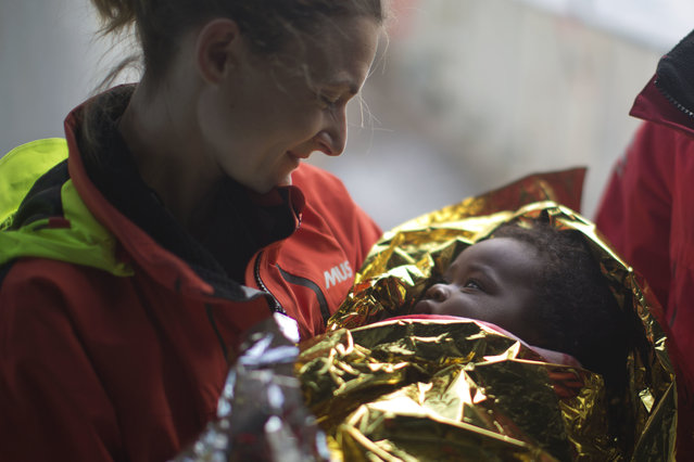 Volunteer Laura Rasero, of Spain, holds two years old Oulai Esther, from Ivory Coast, after been rescued by members of the Spanish NGO Proactiva Open Arms, from a rubber boat sailing out of control in the Mediterranean Sea about 21 miles north of Sabratha, Libya, on Friday, February 3, 2017. European Union leaders are poised to take a big step on Friday in closing off the illegal migration routes from Libya across the central Mediterranean, where thousands have died trying to reach the EU, the EU foreign affairs chief Federica Mogherini said. (Photo y Emilio Morenatti/AP Photo)