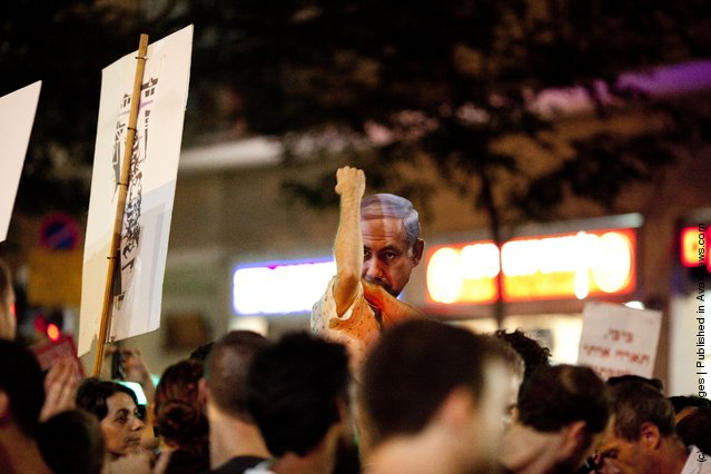 An Israeli man wears a mask of Israel's Prime Minister Benjamin Netanyahu during a protest against rising housing prices and social inequalities on July 30, 2011 in Tel Aviv, Israel