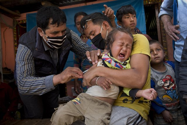 A Nepalese infant is given a vaccination in Lapsiphedi, near Kathmandu, Nepal, Monday, May 4, 2015. A campaign's underway in Nepal to immunize half a million children against measles and rubella in the wake of the earthquake. (Photo by Bernat Amangue/AP Photo)