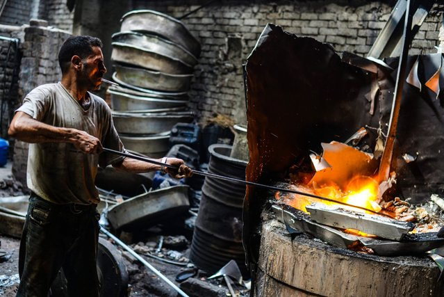 A picture made available on 17 March 2016 shows a worker melting the aluminum at 660 degrees celsius at Mit Ghamr, Dakahlia, 80 km north east of Cairo, Egypt, 13 March 2016. The aluminum industry in Mit Ghamr produces 70% of Egypt's production of Aluminum, with some 45 thousand worker and more than 300 workshops that produce an average 50 thousand tons of aluminum products a year. (Photo by Mohammed Hossam/EPA)