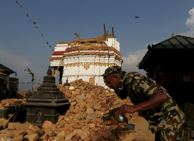 A soldier washes his face after working to repair the ancient Swayambhunath Stupa temple damaged by the April 25 earthquake in Kathmandu, Nepal, May 6, 2015. (Photo by Olivia Harris/Reuters)