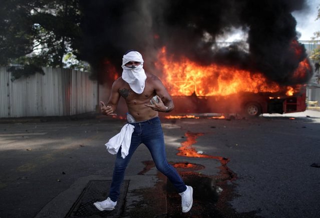 """An opposition demonstrator gestures in front of a burning bus, while holding a rock, near the Generalisimo Francisco de Miranda Airbase """"La Carlota"""", in Caracas, Venezuela April 30, 2019. (Photo by Ueslei Marcelino/Reuters)"""