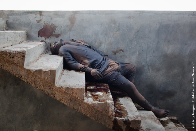 The body of a man lays on a staircase near to a warehouse where burnt bodies were discovered
