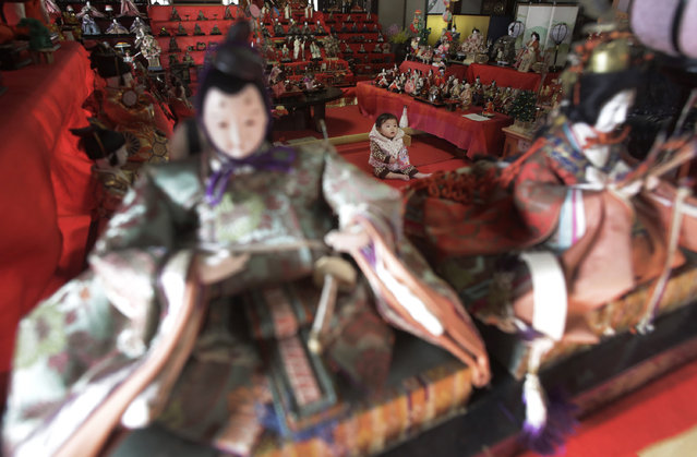 A baby girl sits among the sets of old hina dolls displayed to celebrate the Girls' Festival in Yokohama, southwest of Tokyo, Monday, March 3, 2014. March 3 is celebrated as Girls' Day to pray for the vigorous growth of girls in the family. (Photo by Eugene Hoshiko/AP Photo)