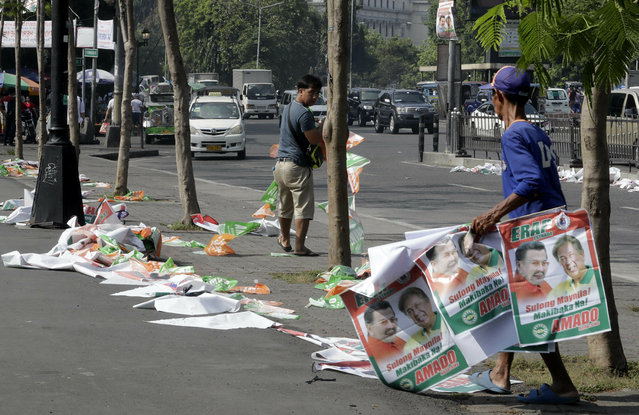 """Manila City public workers remove the campaign posters, mostly that of incumbent Mayor and former President Joseph """"Erap"""" Estrada around the Manila City Hall, a day after the country's midterm elections Tuesday, May 14, 2019 in Manila, Philippines. Estrada lost his third term mayoral bid along with four of his children who ran in local polls, ending his 50-year-dominance in two metropolitan cities in the country. Two of his sons, who ran for senators, are also clinging to the last senate slot in initial results, which were dominated by President Rodrigo Duterte's allies. (Photo by Bullit Marquez/AP Photo)"""