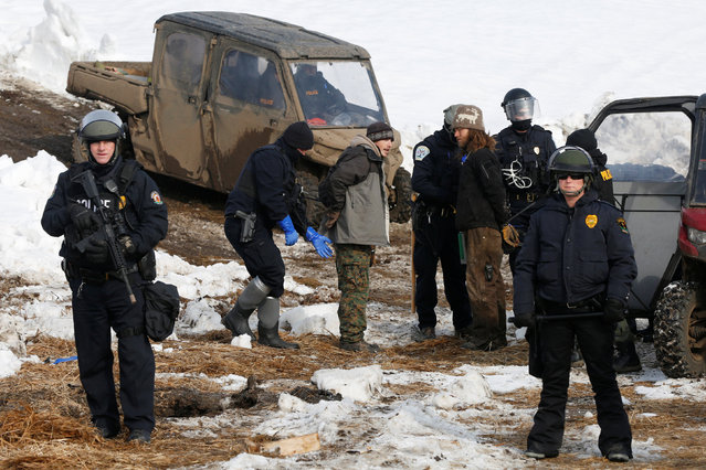 Timothy Powers (C, R) from Southern California is detained with another protester in the main opposition camp against the Dakota Access oil pipeline near Cannon Ball, North Dakota, U.S., February 23, 2017. (Photo by Terray Sylvester/Reuters)
