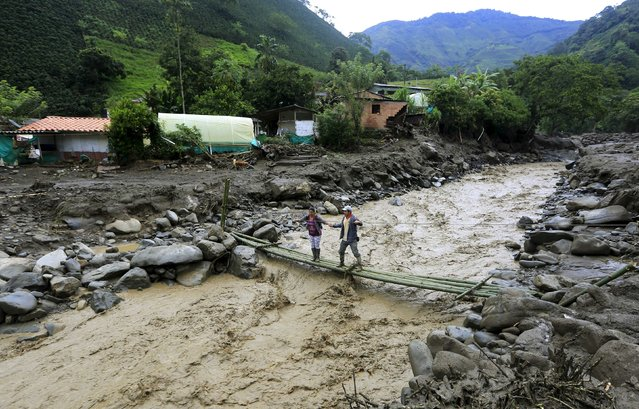 Residents cross over an improvised bridge after a landslide sent mud and water crashing onto homes close to the municipality of Salgar in Antioquia department, Colombia May 19, 2015. (Photo by Jose Miguel Gomez/Reuters)