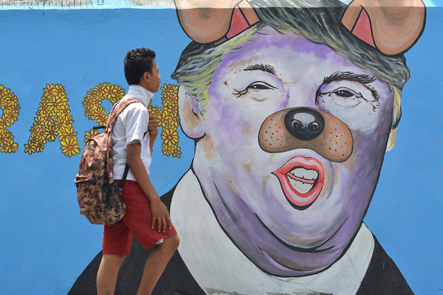 A student passes in front of a mural depicting US President Donald Trump with a nose and ears like a dog at Palu on February 27, 2017 in Central Sulawei, Indonesia. (Photo by Sijori Images/Barcroft Images)