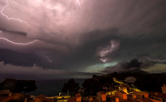 Lightning strike in the dark clouds over the Spanish Balearic island of Mallorca during a heavy thunder storm, near Andratx, Spain, 11 June 2018. (Photo by Cati Cladera/EPA/EFE)