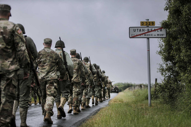 World War II enthusiasts and members of the US Army 4th Infantry Division march toward Utah Beach near Saint-Marie-du-Mont, Normandy, France, Tuesday, June 4, 2019. France is preparing to mark the 75th anniversary of the D-Day invasion which took place on June 6, 1944. (Photo by Rafael Yaghobzadeh/AP Photo)