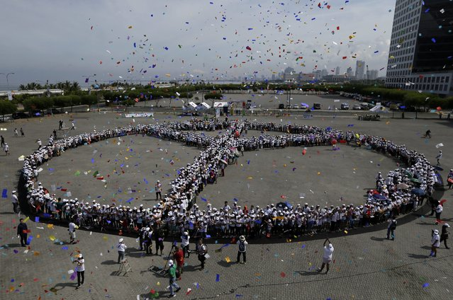 """Confetti fly above Filipinos forming a """"human Peace symbol"""" to celebrate 70 year since the end of the World War II in Pasay city, south of Manila, Philippines, 24 May 2015. The event dubbed """"Handshake for Peace"""" aims to inspire people all over the world to condemn war and continuously crusade for peace. (Photo by Ritchie B. Tongo/EPA)"""