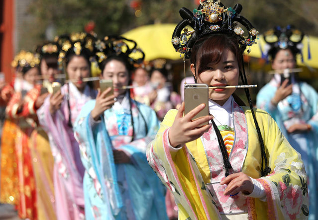 Tour guides wearing traditional Chinese dress practice smiling by biting chopsticks at Qingming Grand-River Park in Kaifeng, central China's Henan Province on March 2, 2017, aiming to provide better service for visitors. (Photo by IPA Asia via ZUMA Wire)
