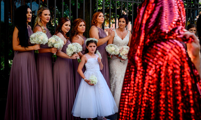 Handsmaid themed protesters march down the French Quarter as a bride and her bridesmaids look on, in New Orleans, Louisiana, on May 25, 2019, to protest the proposed Heartbeat Bill that will ban abortion after 6 weeks in that state scheduled for a vote on May 28. (Photo by Emily Kask/AFP Photo)