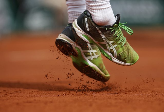 Marsel Ilhan of Turkey jumps to play a shot to Stan Wawrinka of Switzerland during their men's singles match at the French Open tennis tournament at the Roland Garros stadium in Paris, France, May 24, 2015. (Photo by Jean-Paul Pelissier/Reuters)