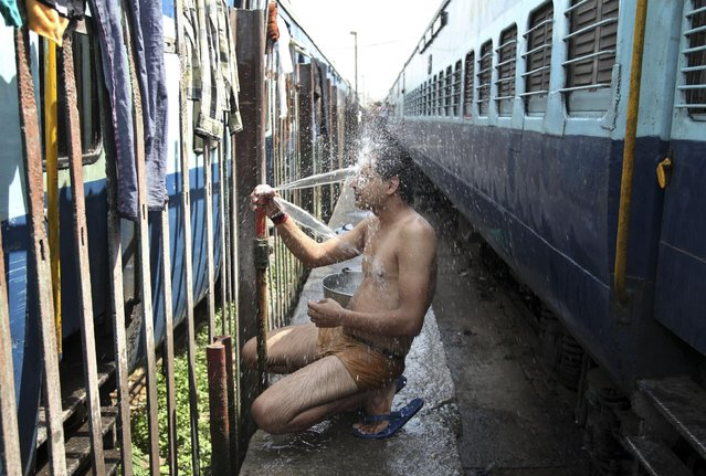 An Indian passenger takes a bath beside rail tracks on a hot summer day at a railway station in Jammu, India, Monday, May 25, 2015. Severe heat wave conditions continue to prevail at several places in northern India with temperatures reaching 48 degrees Celsius (118 degrees Fahrenheit). (Photo by Channi Anand/AP Photo)