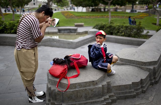 """Regalito"" the clown applies his make up, while his son ""Regalito Junior"" waits for him prior a march commemorating the Peruvian clown day in Lima Peru, Monday, May 25, 2015. (Photo by Rodrigo Abd/AP Photo)"