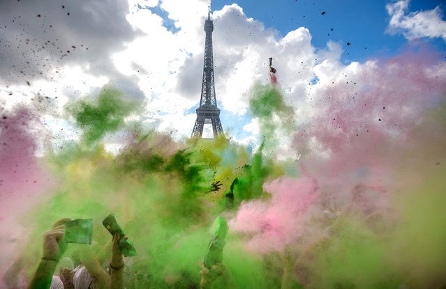 """People covered in colourful chalk powder dance at the finish line after taking part in the Parisian edition of the """"Color Run"""" in Paris, France, 17 April 2016. During the short foot race from the Hotel de Ville town hall to Trocadero across from the Eiffel Tower, runners are doused with colourful chalk. The initiative takes place in many cities around the world. (Photo by Christophe Petit Tesson/EPA)"""