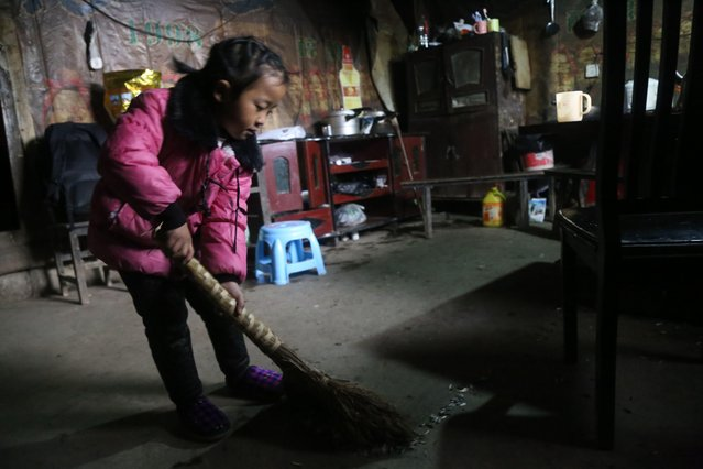 5-year-old Chinese girl Wang Anna cleans at home in Zhuyuan village, Guizhou province, China on March 3, 2017. (Photo by Imaginechina/Rex Features/Shutterstock)