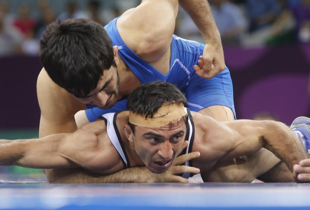 Roman Amoyan of Armenia, bottom, and Elman Mukhtarov of Azerbaijan compete in the the Men's wrestling, 59kg Greco-Roman Bronze Medal event at the 2015 European Games in Baku, Azerbaijan, Saturday, June 13, 2015. (AP Photo/Dmitry Lovetsky)
