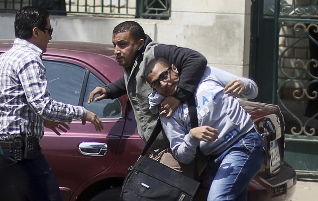 An Egyptian plainclothes policeman detains a student, who is a supporter of the Muslim Brotherhood and ousted President Mohamed Mursi, during a protest against the military and interior ministry in front of the faculty of Oral & Dental Medicine in Cairo University at Kasr El Aini street in downtown Cairo April 9, 2014. (Photo by Amr Abdallah Dalsh/Reuters)