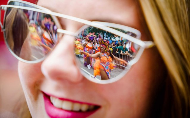 Costumed participants are reflected in a woman's sunglasses during the Summer Carnival Street Parade, which travels through the streets of the center of Rotterdam, the Netherlands, 27 July 2019. Twenty floats participated in the parade with dance acts and lots of music. (Photo by Marco De Swart/EPA/EFE/Rex Features/Shutterstock)