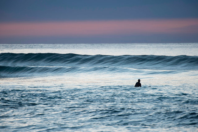 A surfer waits for a wave in Unstad along the northern Atlantic Ocean on March 12, 2017, where the water temperatures is at five degrees centigrade and the air temperature is at minus two degrees centigrade. (Photo by Olivier Morin/AFP Photo)