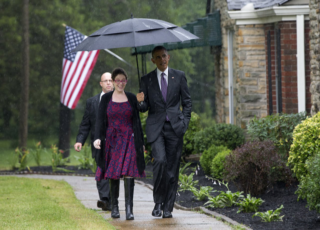 President Barack Obama stops with an umbrella to protect from the rain to pick up Kelly Bryant at her home in Nashville, Tenn., Wednesday, July 1, 2015, en route to Taylor Stratton Elementary School, where he is to speak about the Affordable Care Act. (Photo by Carolyn Kaster/AP Photo)