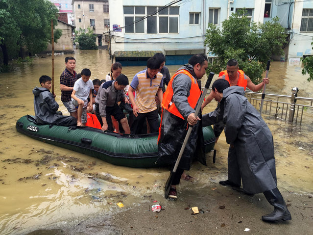 Militia members rescue residents from a flooded neighborhood after heavy rainfall in Yongzhou, Hunan Province, China, May 5, 2016. (Photo by Reuters/Stringer)