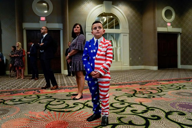 9-year-old Reed Elliotte stands in the back of the room in a U.S. flag outfit with his mother Larrietta listening to U.S. President Donald Trump address the AMVETS American Veterans convention in Louisville, Kentucky U.S. August 21, 2019. (Photo by Kevin Lamarque/Reuters)