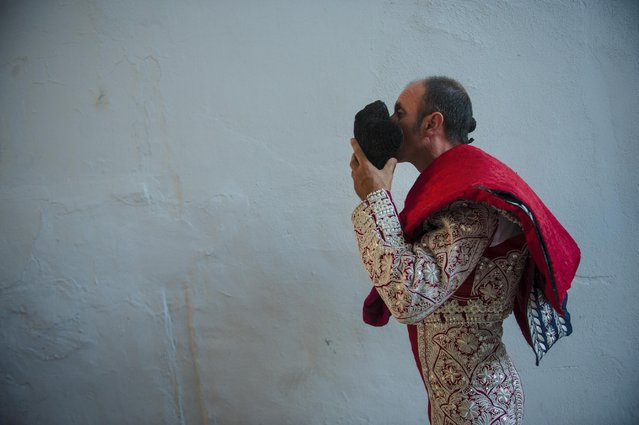 An assistant to a Spanish mounted bullfighter waits on the sidelines during a horseback bullfight at San Fermin Fiestas, in Pamplona, northern Spain, Monday, July 6, 2015. Revelers from around the world kick off the festival with a messy party in the Pamplona town square, one day before the first of eight days of the running of the bulls. (Photo by Alvaro Barrientos/AP Photo)