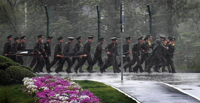 Military personnel run through the pouring rain outside the main airport in Pyongyang, North Korea on May 3, 2016. (Photo by Linda Davidson/The Washington Post)