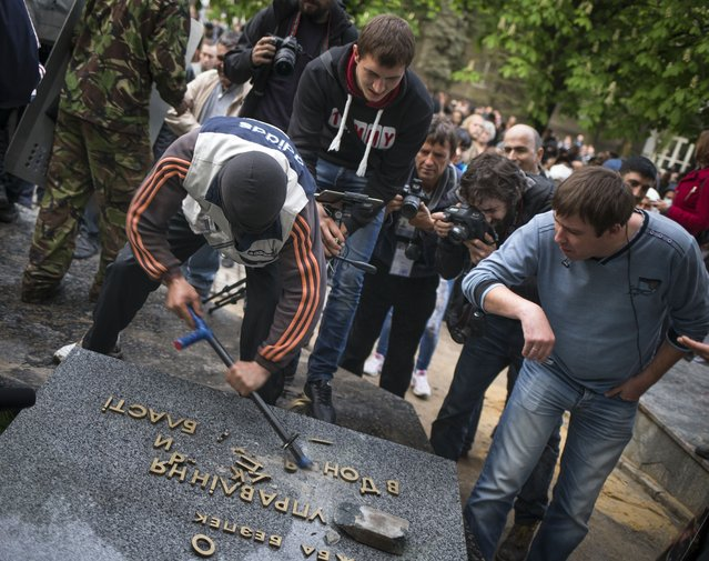 """Pro-Russian protesters break up the words """"Ukrainian the Security Service"""" next to the Ukrainian regional office of the Security Service in Donetsk, eastern Ukraine, Saturday, May 3, 2014, which has been captured to honor the memory of fallen comrades during fighting with pro-Ukrainian activists in Odessa on Friday. (Photo by Alexander Zemlianichenko/AP Photo)"""