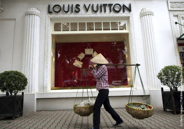 A Vietnamese woman walks by the Louis Vuitton shop in the French quarter