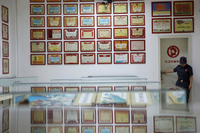 A staff member opens a door by a wall where honorary prize papers bearing the image of late Chinese Chairman Mao Zedong hang, at an exhibition hall at Jianchuan Museum Cluster in Anren, Sichuan Province, China, May 13, 2016. (Photo by Kim Kyung-Hoon/Reuters)