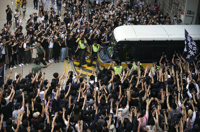 Supporters surround a police bus carrying political activist Edward Leung as it leaves the High Court in Hong Kong, Wednesday, October 9, 2019. Several hundred masked protestors chanting for revolution have gathered at Hong Kong's High Court for the appeal hearing of an activist sentenced to six years in prison for his part in a violent nightlong clash with police. (Photo by Vincent Yu/AP Photo)