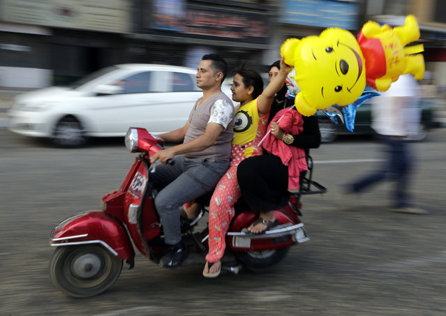Egyptians ride their motorbike as they celebrate Eid al-Fitr feast, marking the end of the Muslim fasting month of Ramadan in Cairo, Egypt, Friday, July 17, 2015. (Photo by Amr Nabil/AP Photo)
