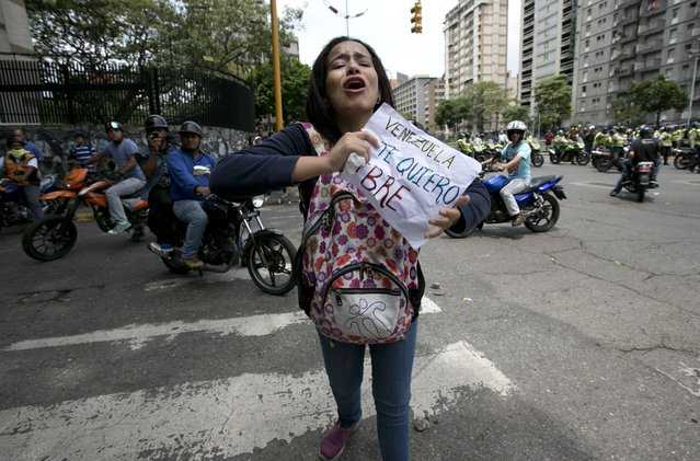 """An anti-government demonstrator holds a sign that reads in Spanish: """"Venezuela I want you free"""" during a march toward the headquarters of the national electoral body, CNE, in Caracas, Venezuela, Wednesday, May 18, 2016. Police blocked protesters trying to reach the CNE to demand a referendum to recall Venezuela's President Nicolas Maduro. (Photo by Ariana Cubillos/AP Photo)"""