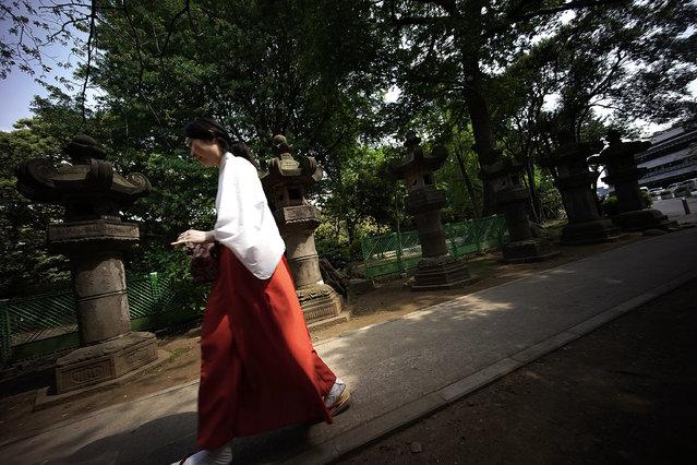 A shrine maiden walks near stone lanterns in Tokyo, Saturday, May 2, 2015. (Photo by Eugene Hoshiko/AP Photo)