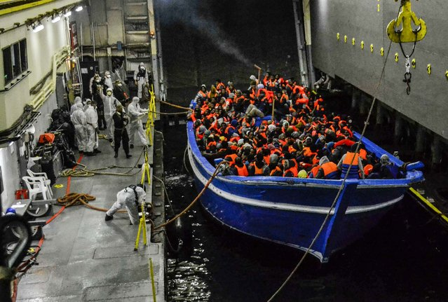 In this photo released by the Italian Navy, a fishing boat filled with migrants is towed into the Navy ship San Giorgio headed to Sicily, on May 22, 2014. (Photo by Italian Navy)