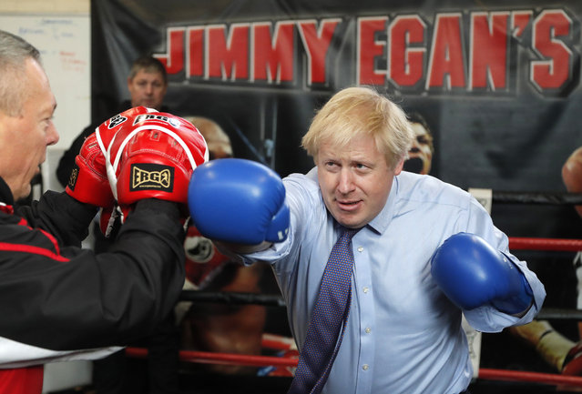 Britain's Prime Minister Boris Johnson works out with trainer Steve Egan during a stop in his General Election Campaign trail at Jimmy Egan's Boxing Academy in Manchester, England, Tuesday, November 19, 2019. Britain goes to the polls on Dec.12. (Photo by Frank Augstein/AP Photo)