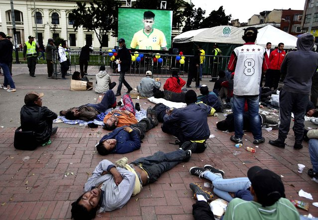 An outdoor screen broadcasts the World Cup game between Brazil and Croatia in an area known as Bronx Street where homeless people gather to watch while others sleep, in downtown Bogota, Colombia. (Photo by Javier Galeano/Associated Press)