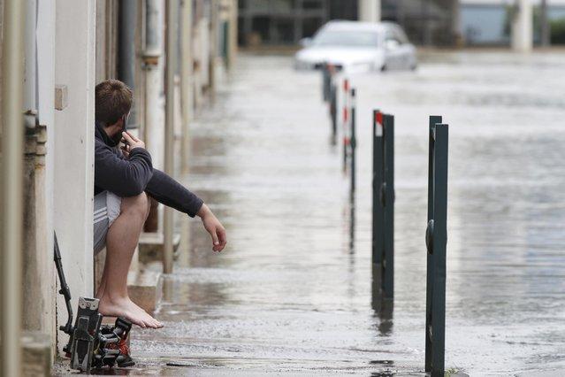 A man sits in front of his house in a flooded street in Montargis in the Loiret, following heavy rain in France June 1, 2016. (Photo by Christian Hartmann/Reuters)