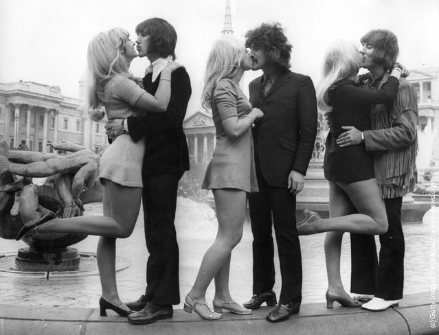 Three members of English pop group The Tremeloes; Chip Hawkes, Alan Blakley and Dave Munden, kissing their brides; Carol Dilworth, Lyn Stevens and Andree Wittenberg, in Trafalgar Square, London, 1967