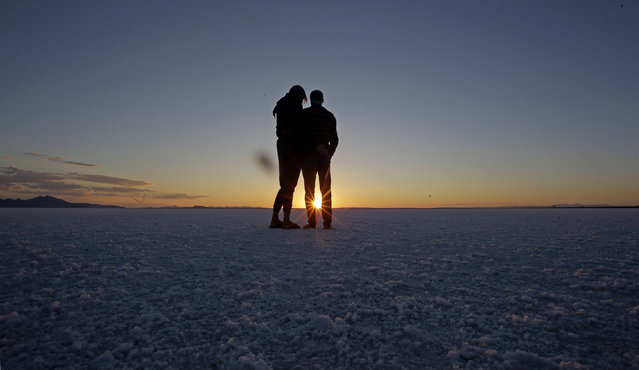 In this Saturday, July 25, 2015 photo, visitors look on as the sun rises on the Bonneville Salt Flats in Utah. (Photo by Rick Bowmer/AP Photo)