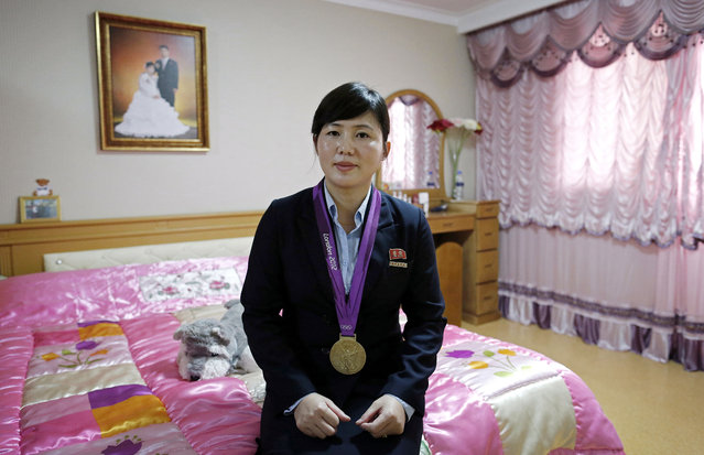 In this October 23, 2014, photo, North Korean London 2012 Olympics Judo gold medalist, An Kum Ae poses in her bedroom with her gold medal in Pyongyang, North Korea. (Photo by Wong Maye-E/AP Photo)