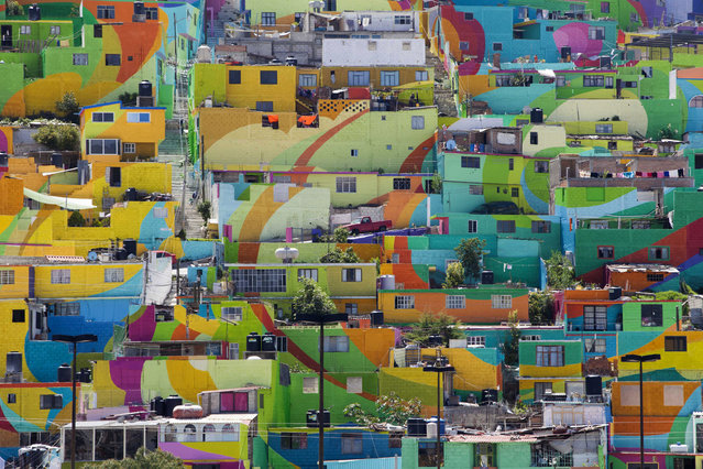 """Hundreds of houses painted in bright colors in what organizers claim is Mexico's largest mural, in the Palmitas neighborhood, in Pachuca, Mexico, Thursday, July 30, 2015. German Crew is the artist collective responsible for the mural project. Director Enrique Gomez, who goes by MYBE, said: """"The mural is a consequence of social integration, participation and community cohesion. Before we started painting with white or colors, we did an analysis of colors and an analysis of the needs we can satisfy through our organization"""". (Photo by Sofia Jaramillo/AP Photo)"""