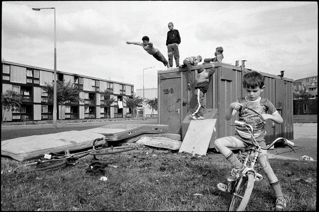 "Moss Side estate, Manchester, England, 1986. Children at play. Stuart Franklin writes: ""The decisive moment, when you think about it, is a one-dimensional concept. It deals with time or timing ... This includes the decisive composition, geometry, quality of light and subject. This picture chimes with the larger meaning and the spirit of Cartier-Bresson's influence on me. I took two or three rolls of film of this scene as it unfolded, but there is only one picture that works, where all the elements come together: timing, composition, geometry and the situation as I wanted to remember it"". (Photo by Stuart Franklin/Magnum Photos)"