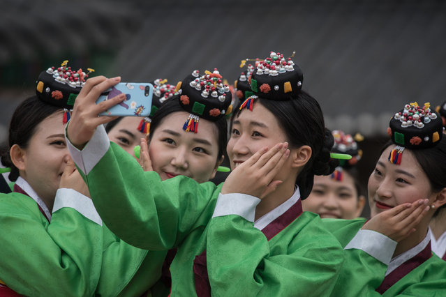 South Korean students pose for a selfie following a traditional coming-of-age ceremony at Namsan hanok village in Seoul on May 15, 2017. (Photo by Ed Jones/AFP Photo)