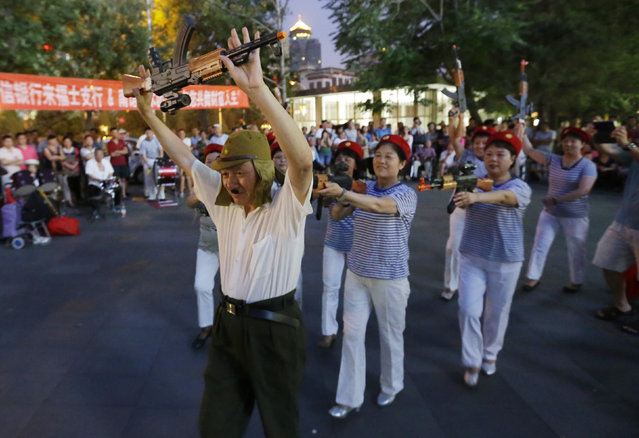 "Chinese women holding toy guns perform an anti-Japanese dance with a man representing as a World War Two Japanese soldier for a revolutionary song during their daily exercise at a square outside a shopping mall in Beijing, June 29, 2014. About 30 local residents formed this ""Nanguan"" art group that enjoys performing to revolutionary songs and dance performances as part of their daily fitness activities at night. (Photo by Jason Lee/Reuters)"